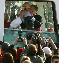 Pope Benedict XVI prepares to bless a child inside the popemobile as he arrives for the celebration of the Eucharist on the former airport site in Freiburg