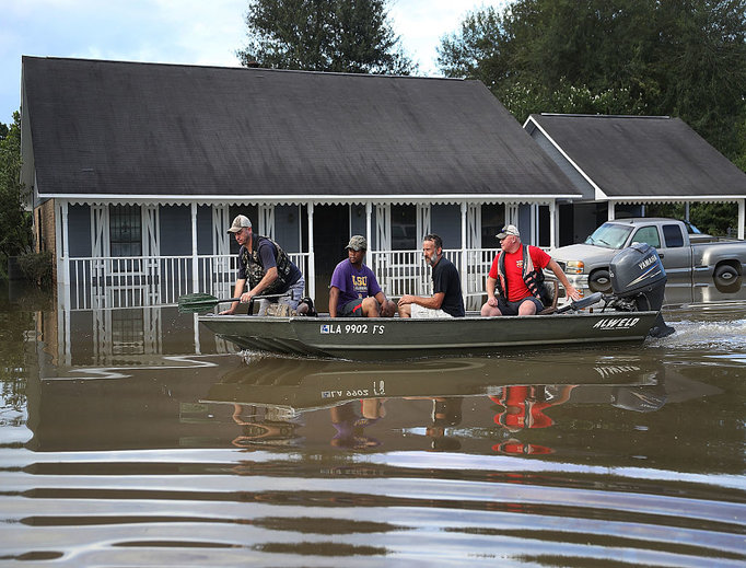 Richard Schafer navigates a boat past a flooded home on Aug. 15 in Baton Rouge, La. Record-breaking rains pelted Louisiana over the weekend, leaving the city with historic levels of flooding that have caused at least seven deaths and damaged thousands of homes.