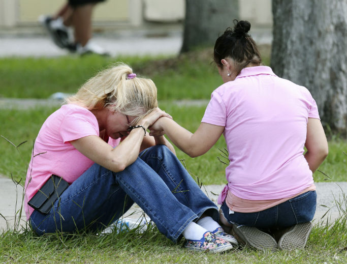 Two women pray outside the family reunification site following a shooting at Santa Fe High School May 18 in Santa Fe, Texas.