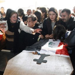 People grieve at the coffins of two Christian brothers killed Nov. 22, during their funeral near Mosul, Iraq. Gunmen shot and killed the two Christians Nov. 23 in the northern Iraqi city in the latest in a spate of attacks targeting the religious minority, Iraqi police said.