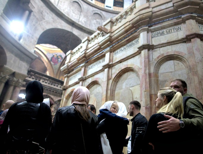 People visit the tomb of Jesus Christ, with the rotunda seen in the Church of the Holy Sepulcher on March 21 in Jerusalem. The tomb, in Jerusalem's Old City, is without its iron cage for the first time since it was placed around the stone tomb by the British in 1947 to keep the Edicule from falling apart.