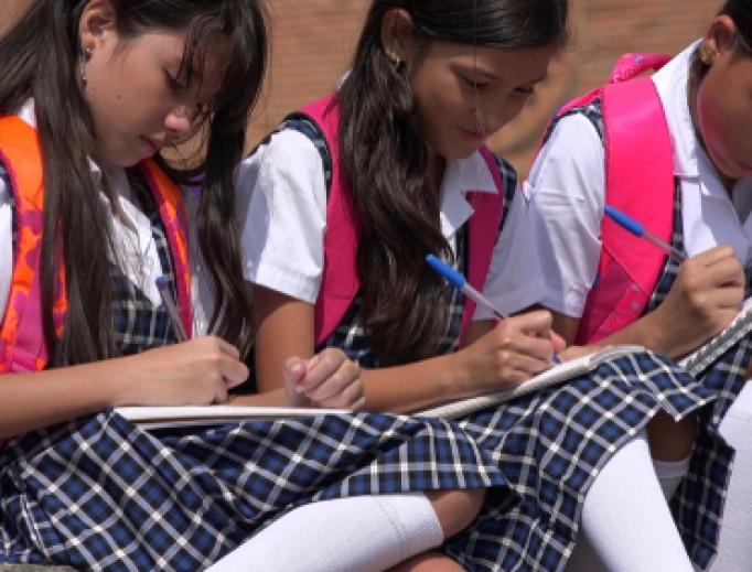 Catholic school girls work on homework outside their school.
