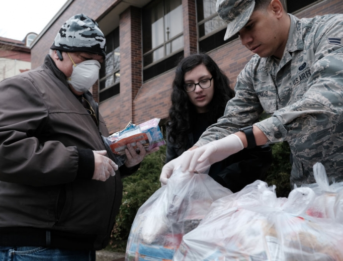 Members of the National Guard hand out bags of food to residents near a 1-mile radius set up to halt the coronavirus (COVID-19) on March 12 in New Rochelle, New York.