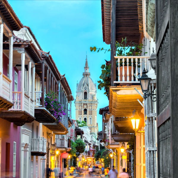 Street view of Cartagena, Colombia, after sunset with cathedral visible in the background.