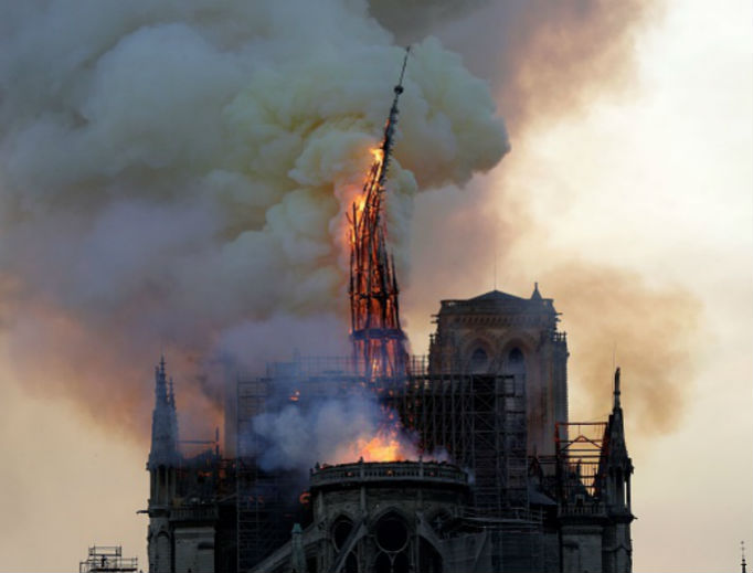 The steeple and spire of the Cathedral of Notre Dame collapses, as the cathedral is engulfed in flames in central Paris on April 15.