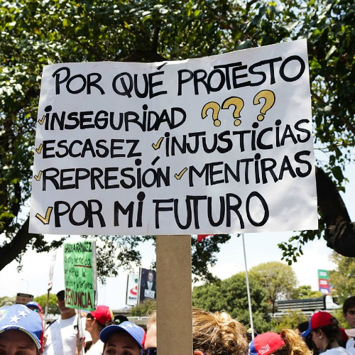 Venezuelan anti-government protesters carry a sign that reads, 'Why do I protest? Insecurity, scarcity, injustices, repression, deceit, for my future.'