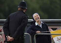 A nun laughs as she chats with a police officer while she waits to see Pope Benedict XVI's popemobile cross Lambeth Bridge in central London Sept. 17.