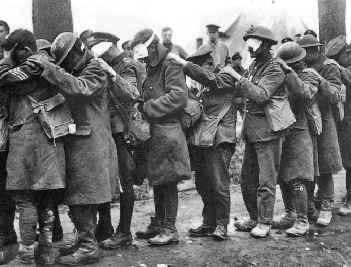 Above, a photograph shows British 55th Division soldiers blinded by tear gas during the Battle of Estaires April 10, 1918; via Imperial War Museums archive. Below, The Last General Absolution of the Munster Fusiliers at Rue du Bois painting was commissioned by Jessie Louisa Rickard; the original was destroyed during the bombing of London in World War II. It was originally published in The Sphere Nov.  27, 1916 (British Library information).