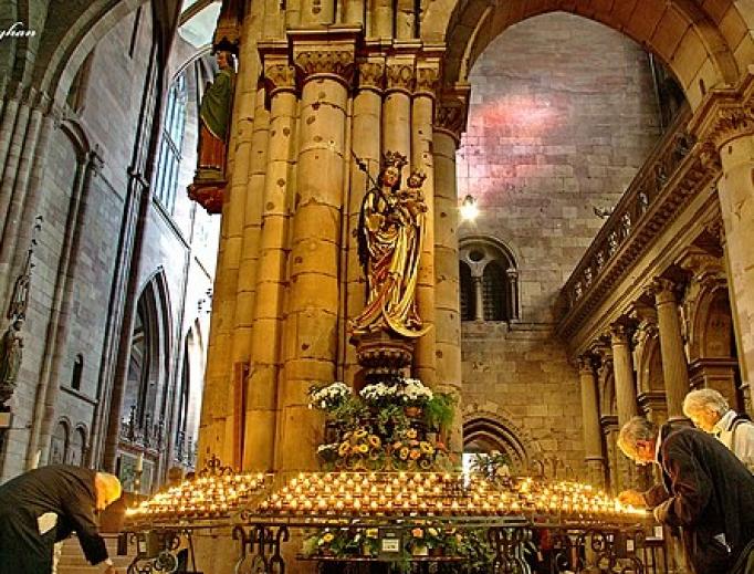 Parishioners light candles inside a Catholic church in Freiburg.