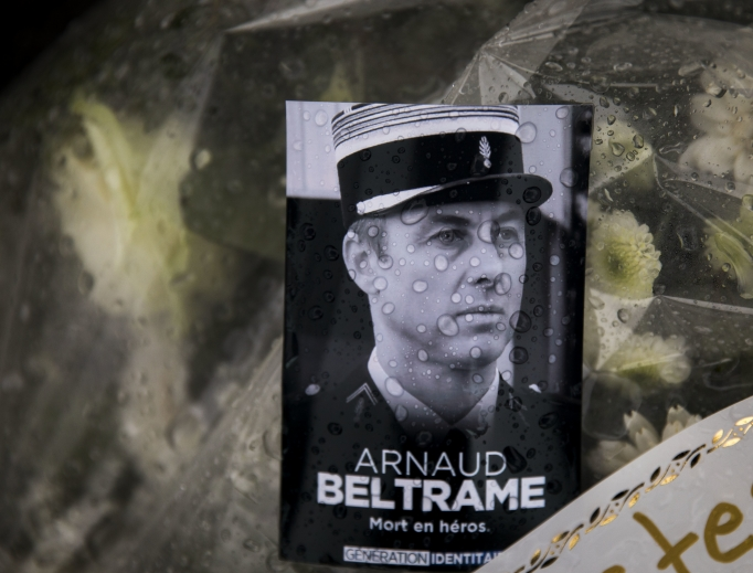 A photo of Lt. Col. Arnaud Beltrame placed on a bunch of flowers at the main gate of the police headquarters in Carcassonne, France, March 24. The French policeman, who offered himself up to an Islamic extremist gunman in exchange for a hostage, died of his injuries, raising the death toll in the March 23 attack to four. The officer, a Catholic, was honored Saturday as a national hero of 'exceptional courage and selflessness.'