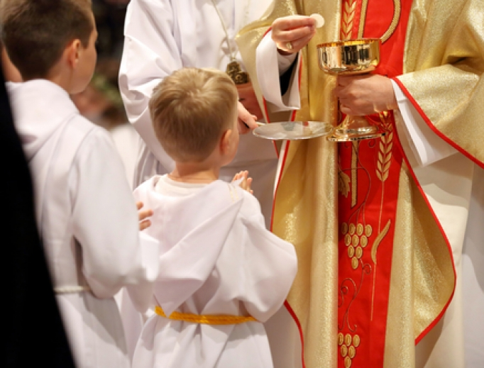 Young children receiving first Holy Communion.