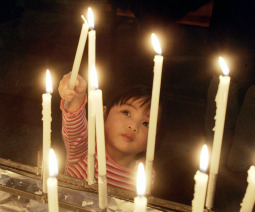 Two-year-old Catherine Louise Niiniaro lights a candle in the parish of St. Maria in Helsinki.
