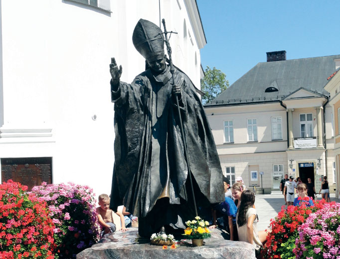 Above, a statue of John Paul II in a Wadowice square. Below, the Wadowice basilica (exterior and interior showing portrait and relics), the John Paul II Family Home Museum and the yellow house where the saint lived in Krakow. Other photos showcase displays at the Wadowice museum, including his skis and rings that John Paul II gave to Benedict XVI and a photo of the papal pair.