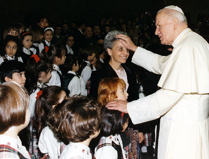Pope St. John Paul II greets a teacher and schoolchildren in 1994 at the Paul VI Audience Hall at the Vatican.