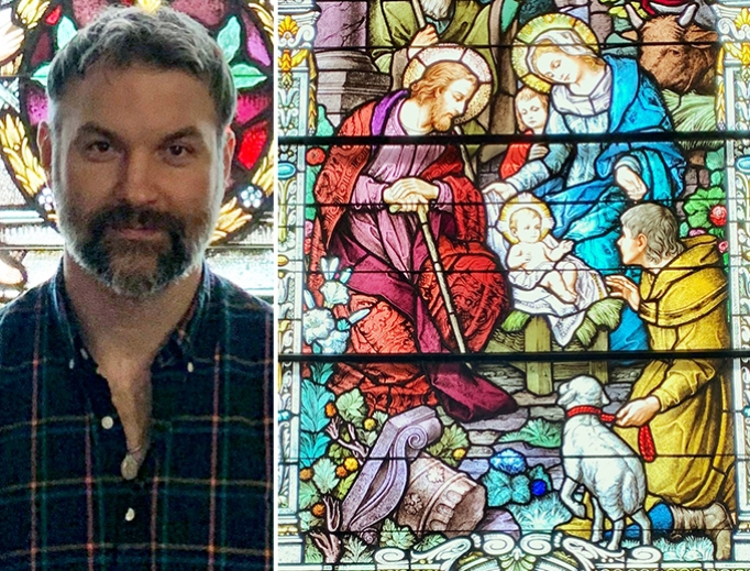 John Scott stands in front of a large stained-glass window at historic Holy Rosary Church in Cedar, Michigan. The right half of the image shows more of the same window.