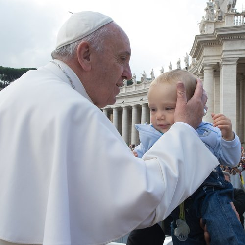 Pope Francis greets a baby at his Oct. 7 Wednesday general audience in St. Peter's Square.