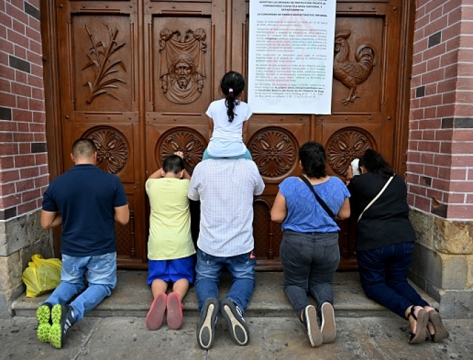 People pray at a door of the closed Basilica of the Lord of Miracles in Buga, Colombia, on March 17, after it was closed as a preventive measure against the spread of the new coronavirus, COVID-19. The Basilica of the Lord of Miracles is one of the most important and most visited religious shrines in the country.