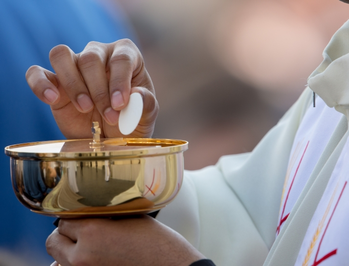 A priest distributes Communion on Divine Mercy Sunday in St. Peter's Square on April 8, 2018.
