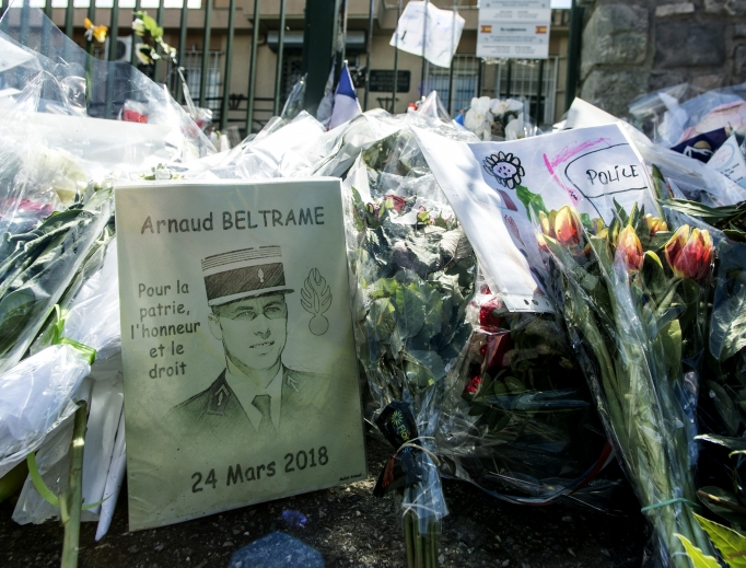 Flowers and a portrait lay at the gate of Lt. Col. Arnaud Beltrame's barracks in Carcassonne, France, March 29. French officials attended the funerals in southern France for the four victims of last week's extremist gun rampage. On Wednesday, France held a national homage to Beltrame, who was given a posthumous Legion of Honor for his heroism in swapping himself for a hostage and potentially preventing further killings.