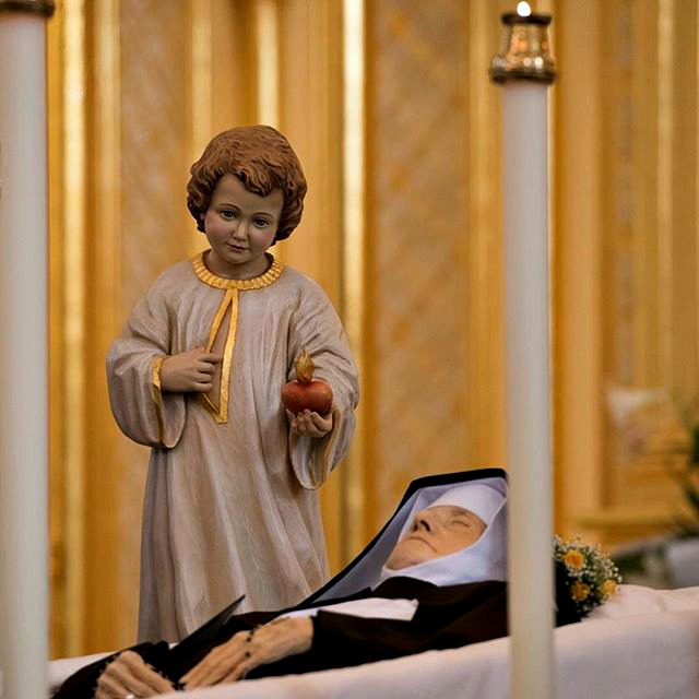 A statue of the Divine Child stands near Mother Angelica as she lays in repose at the Shrine of the Most Blessed Sacrament in Hanceville, Ala., on March 30.