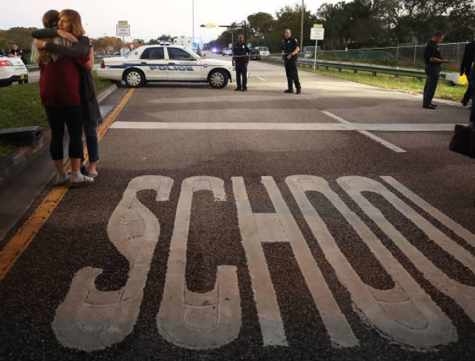 Kristi Gilroy (r) hugs a young woman at a police check point near Marjory Stoneman Douglas High School, where 17 people were killed by a gunman Feb. 14 in Parkland, Florida. Police arrested the suspect after a short manhunt and have identified him as 19-year-old former student.