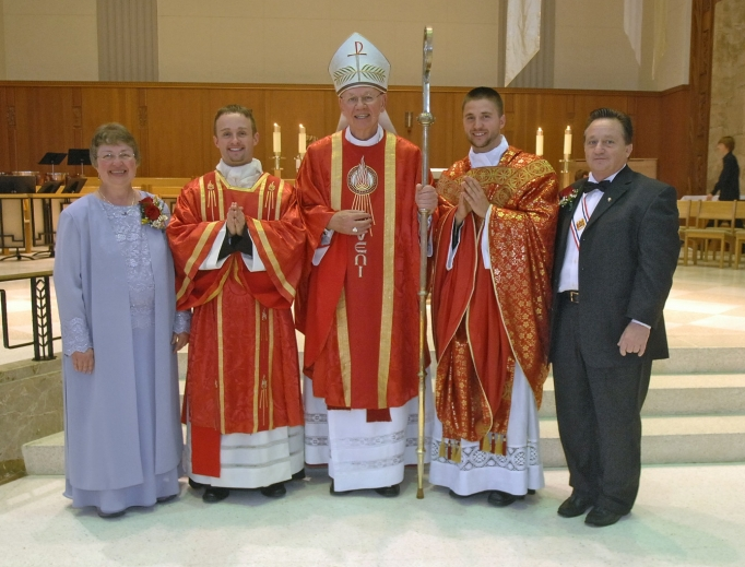 Father Justin (next to his mother) and Father Joshua Waltz (next to his father), shown with their parents, Herb and Theresa. Bishop Paul Zipfel presided at the Cathedral of the Holy Spirit in Bismarck, North Dakota. Below, framed manutergia in the Waltz home: one is behind, showing around the edges. Also shown: Father Jordan Dosch at his first Mass, June 1, at Cathedral of the Holy Spirit, presents the special cloth to his mother, Lynne Dosch. He had just explained the custom before presenting it to his mother. His father, Vernon, is to the left of Lynne.