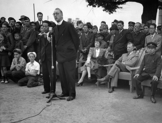 Father Edward Flanagan, founder of Boys Town, Nebraska, speaks into a microphone at Meiji Stadium in Tokyo May 28, 1947, during a Japanese Boy Scout jamboree. At right, wearing his school uniform, is Crown Prince Akahito.