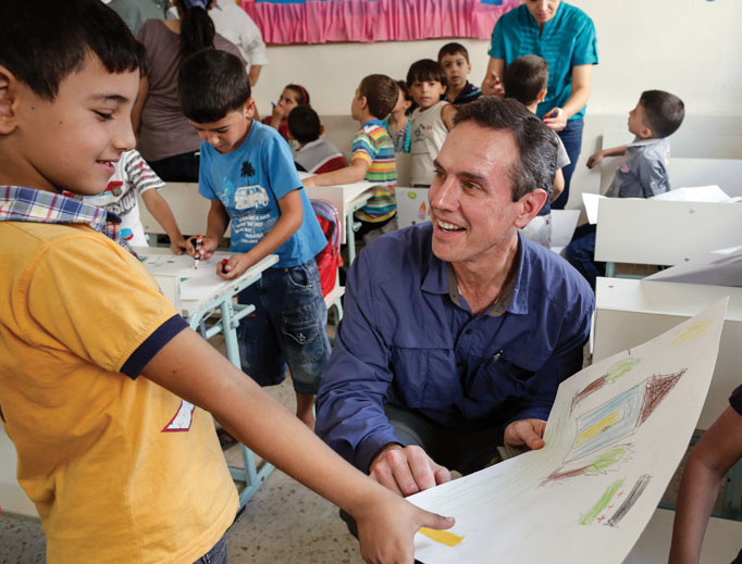 Sean Callahan (also shown below) speaks with young Syrian refugees at a school in Zarqa, Jordan.