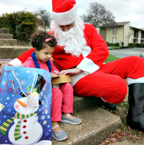 Newly arrived Syrian refugee Jory, 4, receives a gift outside her family's apartment from volunteer Tim Blystone, portraying Santa Claus, on Dec. 12 in Dallas.