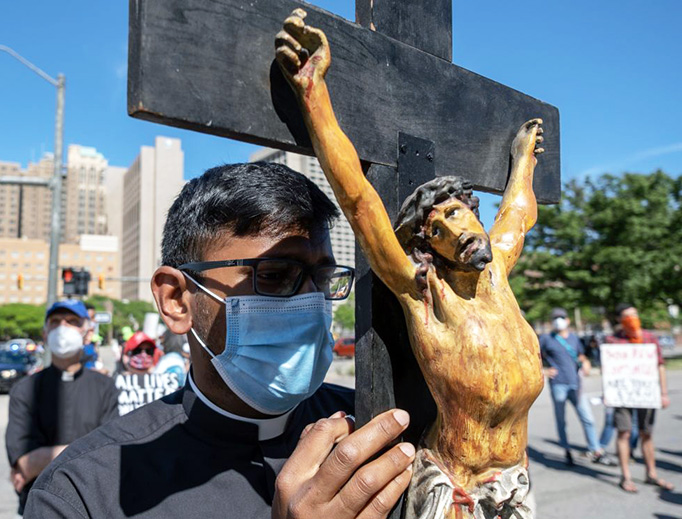 A seminarian holds a crucifix in Detroit during a protest Sunday in memory of George Floyd.