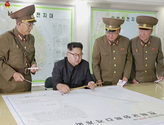 """This image made from video of an Aug. 14 still image broadcast in a news bulletin on Aug. 15 by North Korea's KRT shows North Korean leader Kim Jong Un receiving a briefing in Pyongyang. North Korea said the leader was briefed on his military's plans to launch missiles in waters near Guam days after the Korean People's Army announced its preparing to create """"enveloping fire"""" near the U.S. military hub in the Pacific. Independent journalists were not given access to cover the event depicted in this photo."""