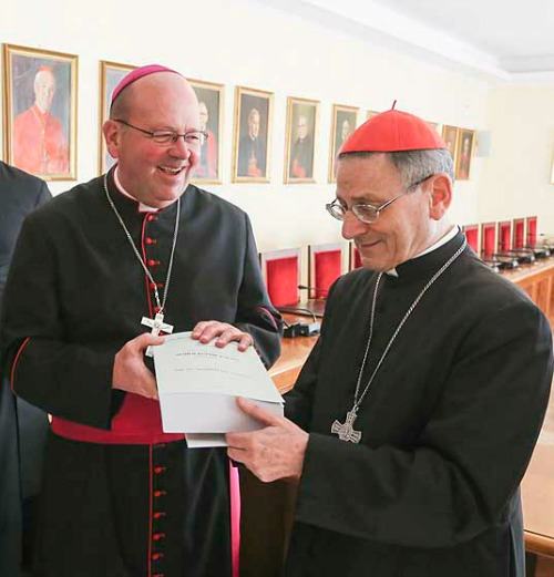 Bishop Carl Demme of Wichita, Kan., presents Father Emil Kapaun's positio to Cardinal Angelo Amato, prefect of Congregation for the Cause of Saints, on Dec. 9 at the Vatican.