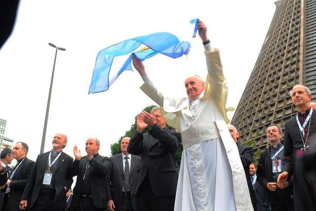 Pope Francis waves an Argentine flag July 25, 2013.