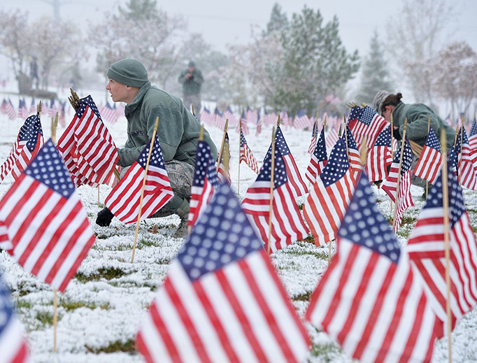 Airmen from Hill Air Force Base place flags beside gravestones at the Utah Veterans Memorial Cemetery, Bluffdale, Utah, Nov. 10, 2015. More than 5,000 flags were placed during the detail in honor of veterans and their families.