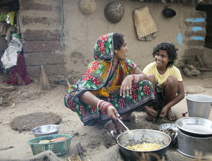 Above, Priyanka Baliar Singh, 12, with her mother, Megharani (Megha) Baliar Singh, as she cooks outdoors. Below, Priyanka plays with her cousin outside of her home. CRS helps parents keep their families together.