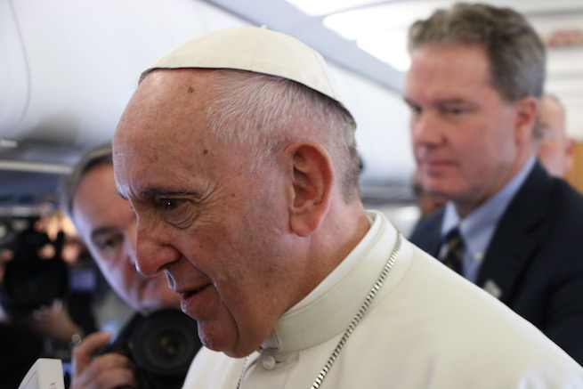 Pope Francis, with Vatican spokesman Greg Burke in the background, speaking to journalists aboard the papal plane to Sweden.