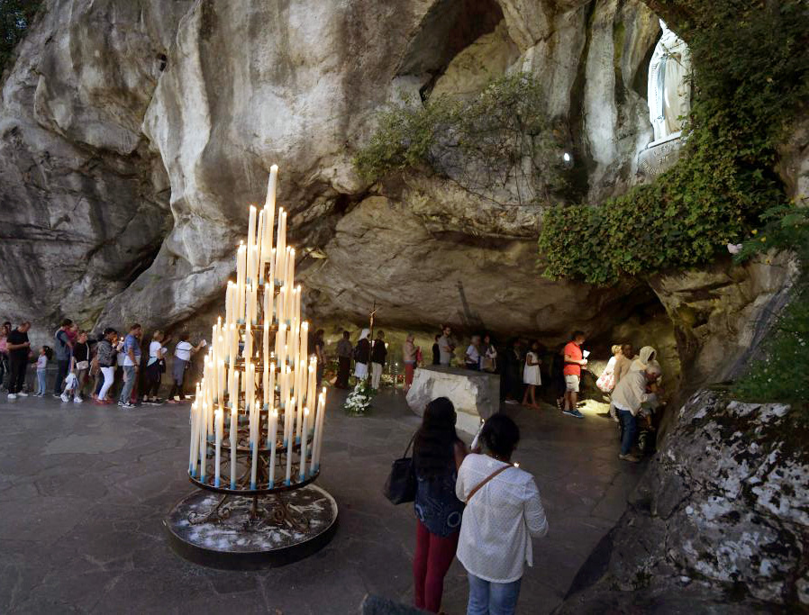 Pilgrims gather Aug. 14, 2019, at the cave in Lourdes where the Blessed Virgin Mary appeared to St. Bernadette Soubirous.