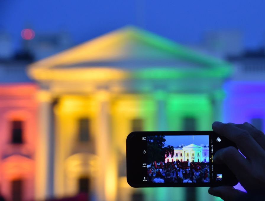 A PICTURE THAT DEFINES A DECADE. A person uses a smartphone to take a photo of the White House lit in rainbow colors, June 26, 2015, following the U.S. Supreme Court's Obergefell decision mandating same-sex marriage nationwide.