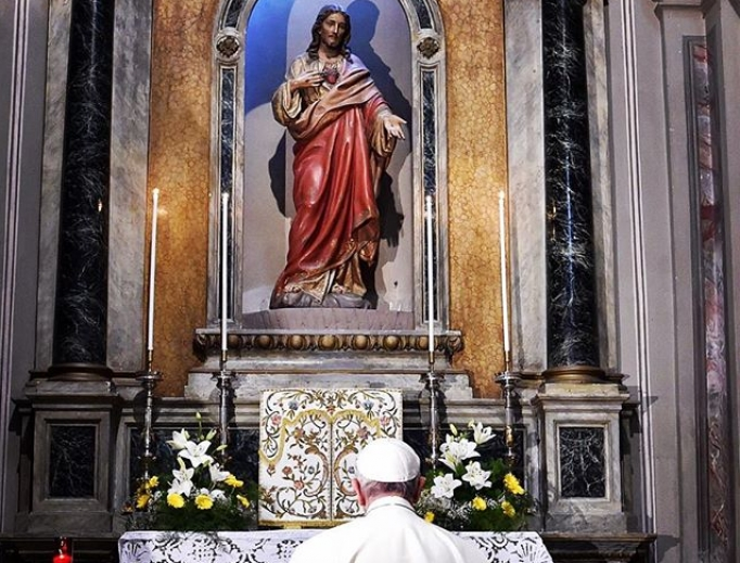 Pope Francis prays before Sacred Heart of Jesus statue.