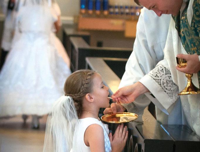 At Sacred Heart Church in Salisbury, North Carolina, first communicant Raegan Glenn receives Communion at the altar rail from Father John Eckert.