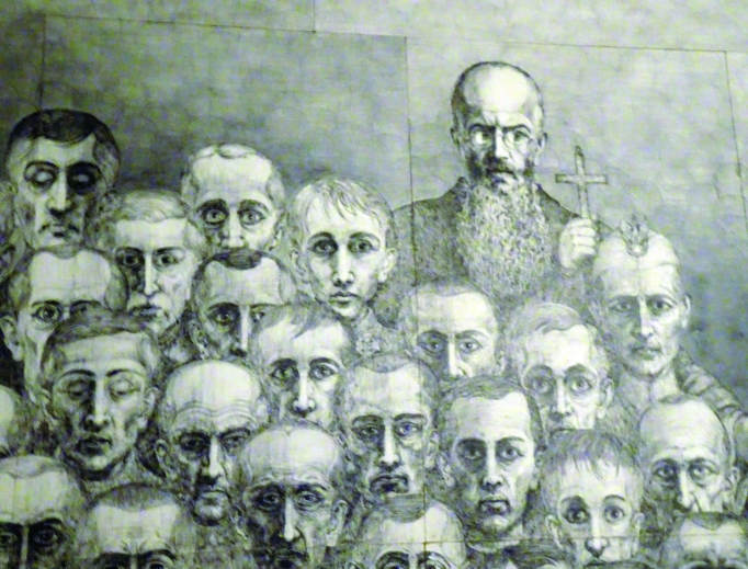 Polish Catholic artist Marian Kołodziej, who survived imprisonment in Auschwitz, created art that showcases the horrors he and millions of others, including St. Maximilian Kolbe, endured at the hands of the Nazis. His artwork is featured by the Franciscans in Harmeze, Poland; the grounds also include Kołodziej's statues of St. Maximilian and the Blessed Mother. Franciscan Father Piotr Cuber (shown) explains the exhibit to visitors.