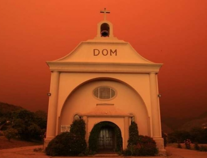 St. Vincent de Paul parish in Davenport, California, surrounded by an orange glow from an approaching fire.