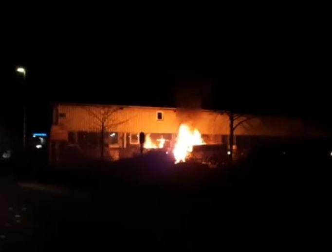 A vehicle on fire in front of a church in Tübingen.