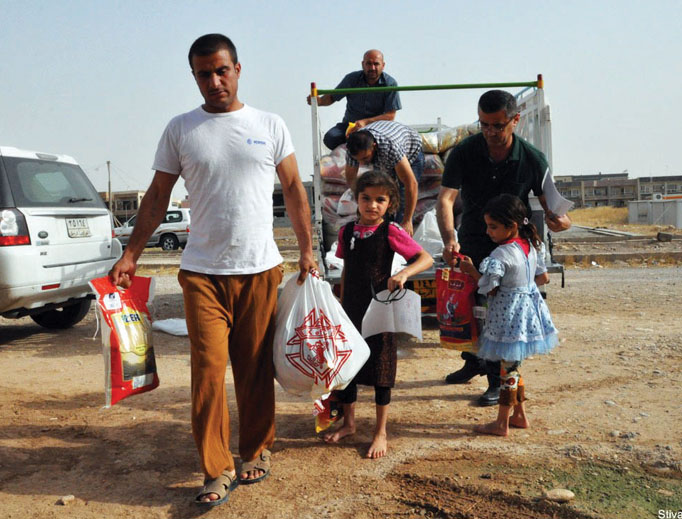 Members of the Archdiocese of Erbil, Iraq, distribute food parcels funded by the Knights of Columbus.