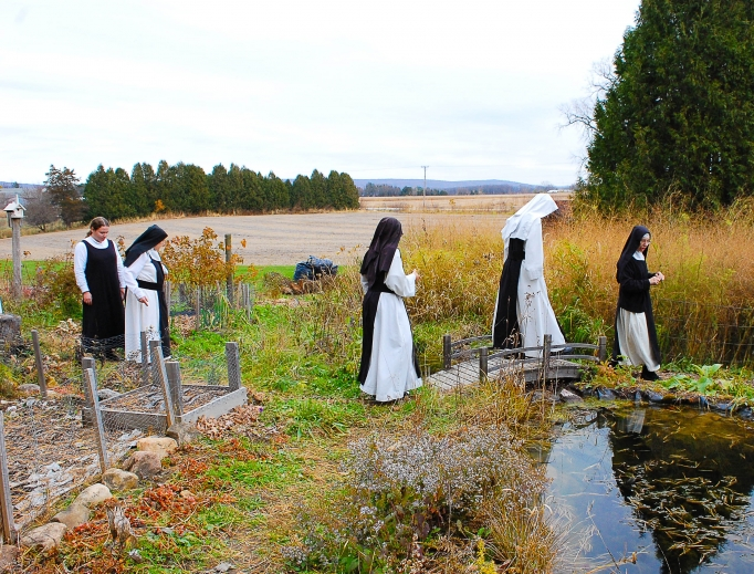 Valley of Our Lady Cistercian Monastery is attracting millennial vocations, offering peace and solitude for garden walks and processions with and adoration of the Blessed Sacrament and  praying of the Divine Office in choir. Also shown: Sister Mary Bede prostrates during her solemn profession on Nov. 17, 2012. Saying the prayers of solemn consecration was the sisters' abbot at that time, Abbot Anselm of the Abbey of Mehrerau, in Austria, the head of the sisters' congregation. The sisters belong to a group of Swiss-Austrian-German monasteries.