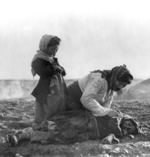 An Armenian woman kneels beside a dead child near the city of Aleppo, during the genocide carried out by the Ottoman Empire against Armenians that began in April 1915.