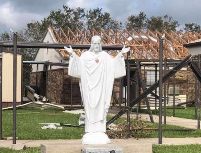 Statue of Jesus in front of damaged church property in the Diocese of Lake Charles.
