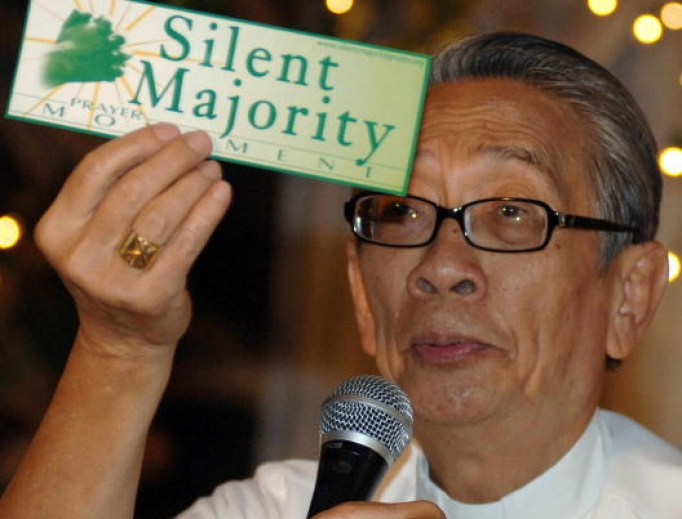 """Philippine Archbishop Oscar Cruz shows a sticker during the launching of the """"silent majority prayer movement"""" movement in a pressconference in Manila 26 January 2006 calling on the Catholic Filipinos to pray for the welfare of the country amid a political crisis surrounding President Gloria Arroyo's government ."""