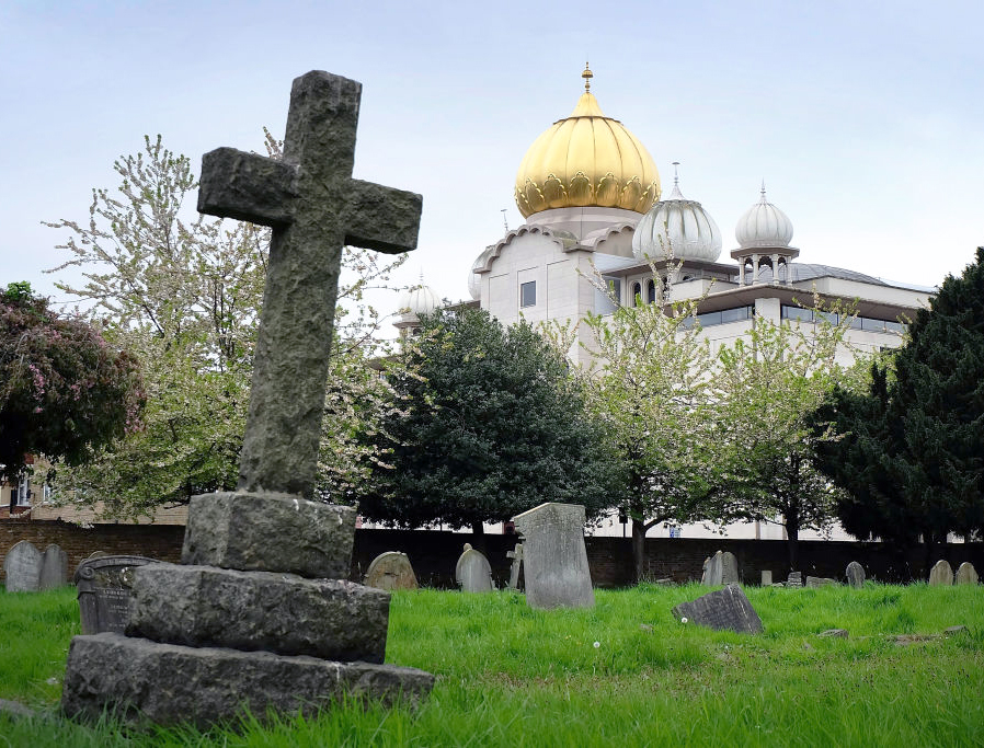 The golden dome of the Sri Guru Singh Sabha Sikh temple in Southall rises up behind the graves of Havelock cemetery, on April 22, 2017 in London, England.