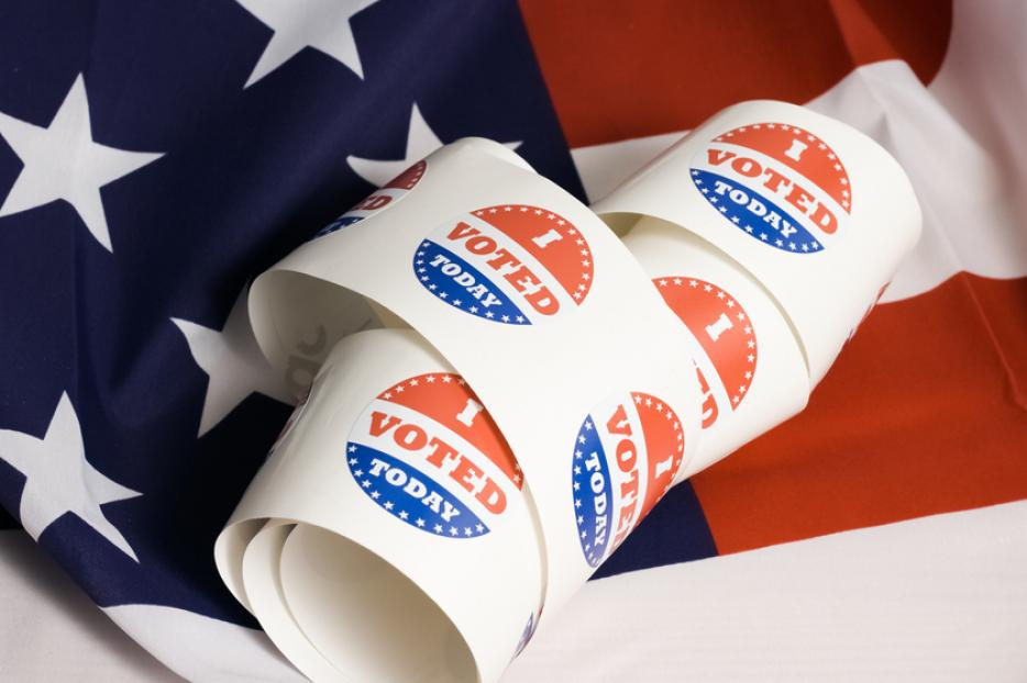 Voting stickers spiral against an American flag.